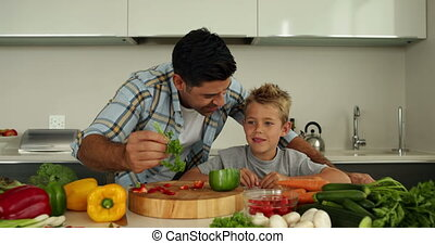 Father showing his son different ingredients at home in the...