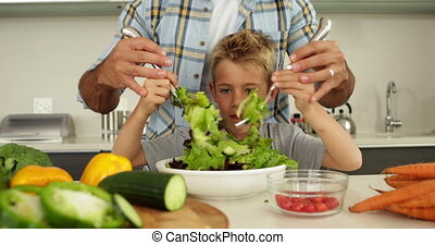 Father showing his cute son how to toss a salad at home in...