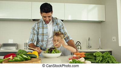 Father showing his son how to toss a salad at home in the...