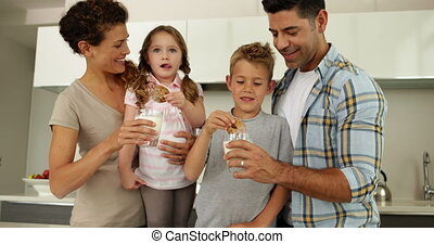 Children having milk and cookies with their parents at home...