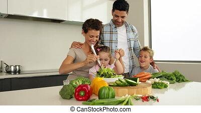 Parents making a salad with their children at home in the...