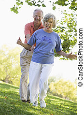 Senior couple having fun in park running on grass