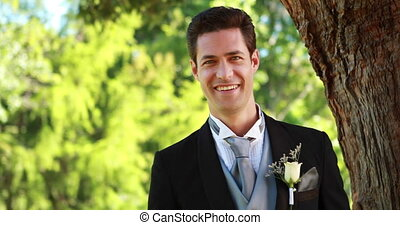 Happy groom smiling at camera on a sunny day