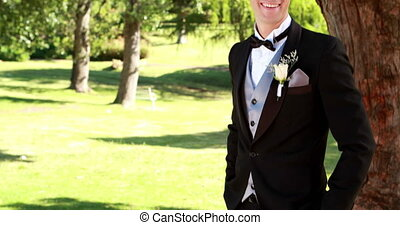 Attractive groom smiling at camera on a sunny day