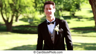 Attractive groom walking towards and smiling at camera on a...