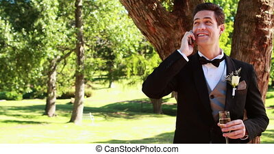Happy groom drinking champagne and chatting on phone on a...