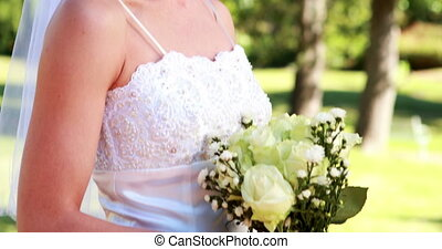 Bride holding a bouquet in the park smiling at camera on a...