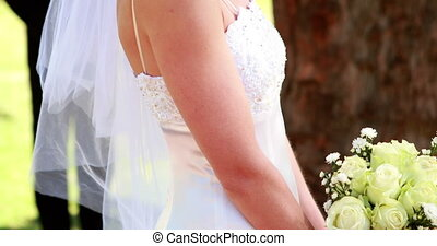 Bride smiling at camera with groom standing in background on...
