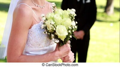 Pretty bride smiling at camera with groom standing in...