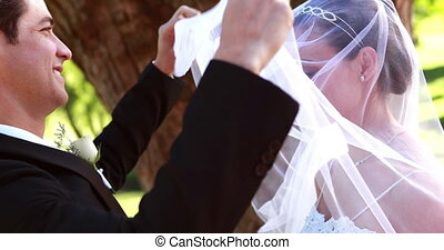 Groom lifting his brides veil and kissing her on a sunny day