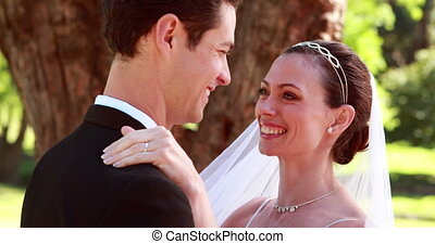Young newlyweds dancing together and smiling on a sunny day