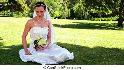 Content bride sitting on the grass on her wedding day