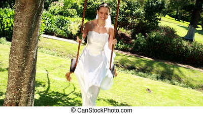 Smiling bride sitting on a swing lo