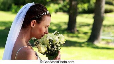 Smiling bride smelling her bouquet - Smiling bride smelling...