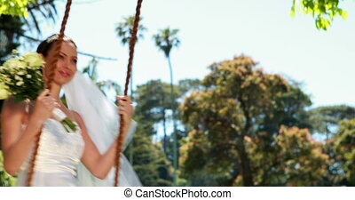 Pretty bride sitting on a swing smiling at camera on her...