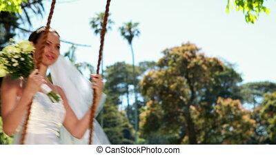 Pretty bride sitting on a swing sm