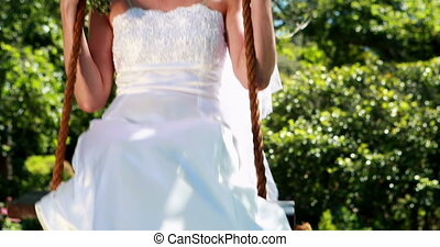 Happy bride sitting on a swing looking at camera on her...