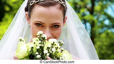 Pretty bride smiling at camera and smelling her bouquet on...