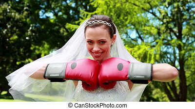 Pretty bride smiling at camera and wearing boxing gloves on...