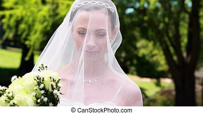 Pretty bride smiling at camera with veil over her face on...
