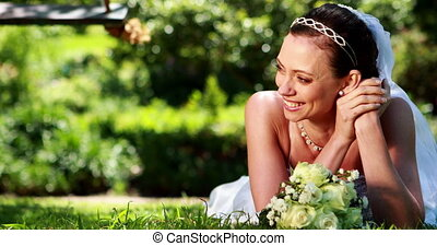 Beautiful bride smiling at camera lying on the grass on her...