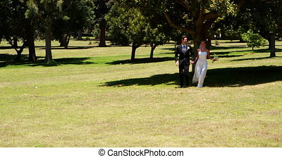 Excited newlyweds running towards the camera on their...