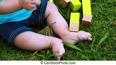 Baby boy playing with building blocks on the grass on a...