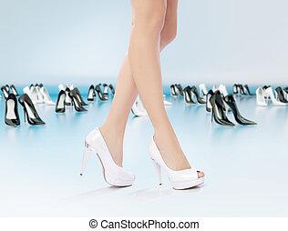 Sexy female legs among high-heel shoes