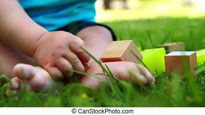 Baby playing with building blocks on the grass on a sunny...