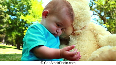 Cute baby boy playing with teddy bear on a sunny day