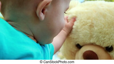Adorable baby boy playing with teddy bear on a sunny day