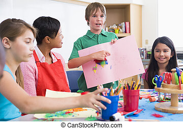 Elementary pupil discussing picture with classmates
