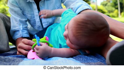 Mother playing with her cute baby son on picnic blanket on a...