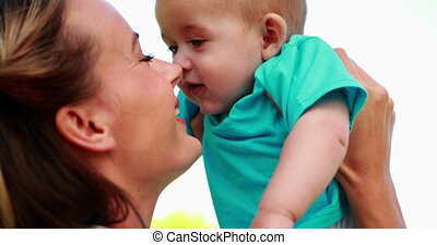 Happy mother rubbing noses with cute baby son in the park on...
