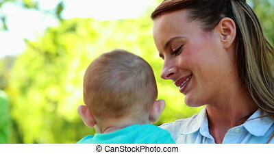 Happy mother holding cute baby son in the park on a sunny...