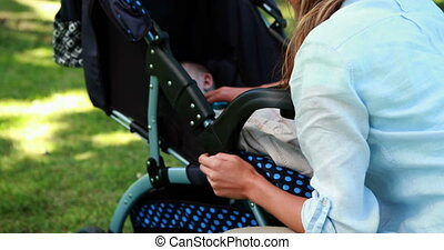 Mother checking on her sleeping baby in a pram in the park...