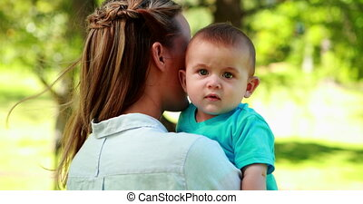 Mother holding baby son in the park