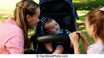Mother and daughter playing with baby in a pram in the park...