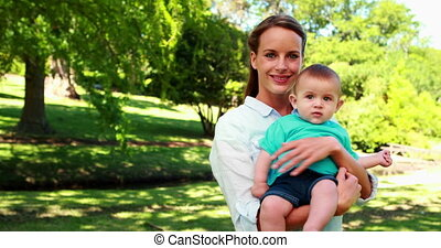 Happy mother holding cute baby son smiling at camera on a...
