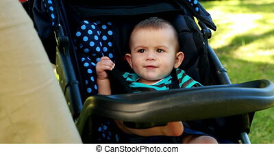 Little baby boy sitting in his pram