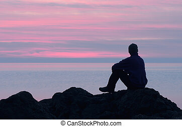 Guy looks at the sunset - Evening at the seaside. Guy sits...