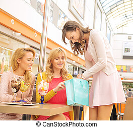 Attractive lady showing her girlfriends some shopping -...