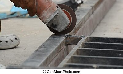 Metal worker - A worker cuts a metal part in two pieces with...