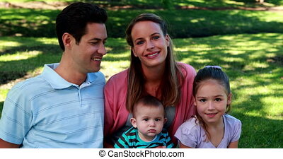 Young family smiling at the camera in the park on a sunny...