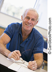 Mature male student holding glasses in class