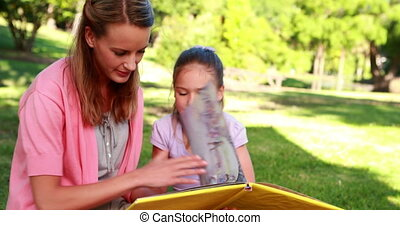 Little girl reading storybook with her mother in the park on...