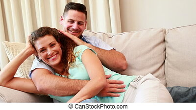 Cuddling couple on the couch at home in the living room