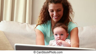 Mother using laptop with baby son o