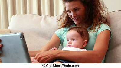 Mother using tablet pc with baby son on her lap at home in...