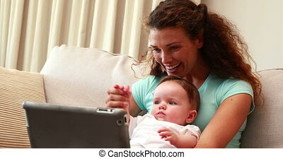 Mother using tablet pc for video ch